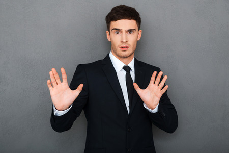 Stop it! Frustrated young man in formalwear keeping arms raised and expressing negativity while standing against grey background Stock Photo