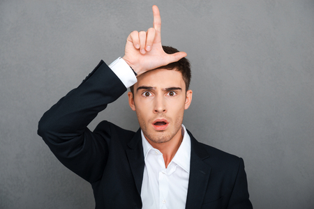 l hand: Loser! Frustrated young man in formalwear gesturing loser sign and looking at camera while standing against grey background Stock Photo