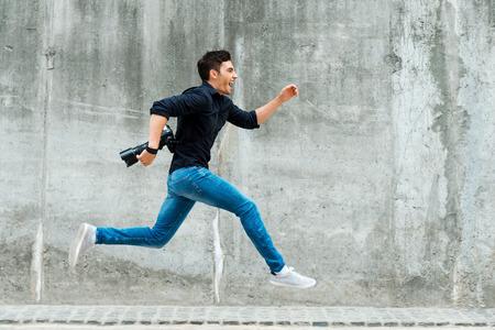 Haasten om de eerste te zijn. Volledige lengte van de jonge fotograaf lopen tegen een betonnen muur Stockfoto