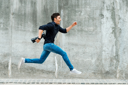 man side view: Hurrying to be first. Full length of young photographer running against a concrete wall