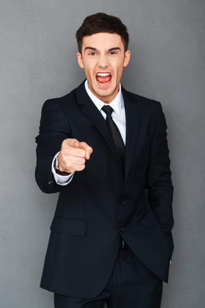 formalwear: Go away! Angry young man in formalwear pointing at camera and screaming while standing against grey background Stock Photo