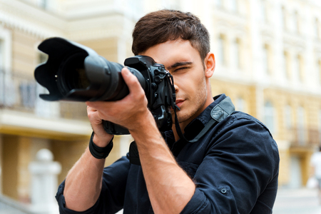 Photography is my passion. Confident young man photographing something while standing outdoors Stockfoto