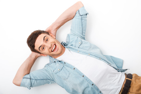 hands on head: So happy and carefree. Top view of cheerful young man holding hands behind head and smiling while lying on white
