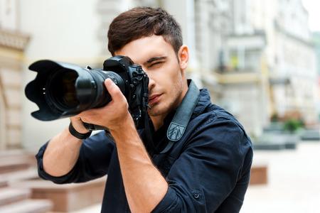 Gotowy do strzału. Przekonany, młody człowiek fotografuje coś stojąc na zewnątrz Zdjęcie Seryjne