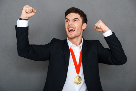 expressing positivity: Always first. Happy young man in formalwear keeping arms raised and expressing positivity while standing against grey background