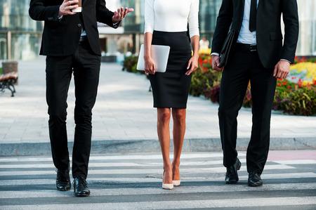 empleado de oficina: Caminando hacia el �xito. Imagen recortada de tres hombres de negocios que cruza la calle