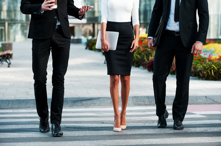 white collar worker: Walking to success. Cropped image of three business people crossing the street Stock Photo