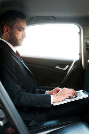 go inside: Businessman on the go. Confident young businessman working on laptop while sitting inside his car