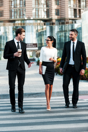 On the way to success. Full length of three smiling business people talking to each other while crossing the street