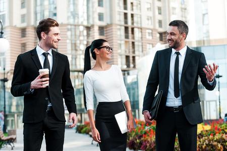 사람들: 회의 전에 빠른 브리핑. 야외에서 산책하는 동안 서로 얘기하는 세 쾌활한 젊은 비즈니스 사람들