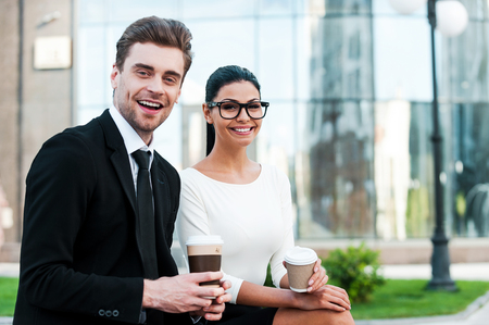 business people: Enjoying coffee break. Two happy young business people holding cups of coffee and looking at camera while sitting outdoors Stock Photo