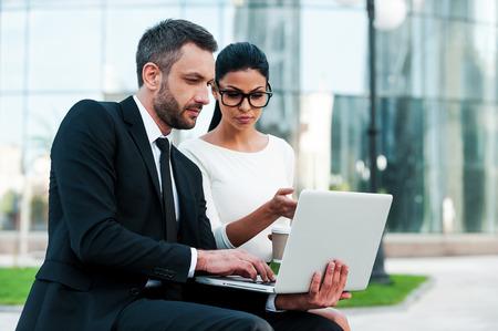 함께 비즈니스 프로젝트를 논의했다. 야외 앉아있는 동안 노트북에서 작업하는 두 확신 젊은 비즈니스 사람 스톡 콘텐츠