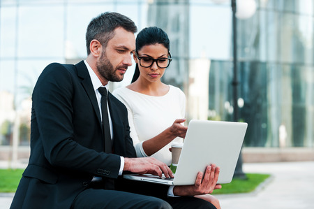 business executive: Discussing business project together. Two confident young business people working on laptop while sitting outdoors Stock Photo