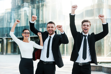 expressing positivity: We did it! Three exited young business people keeping arms raised and expressing positivity while standing outdoors with office building in the background
