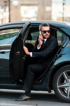Yo ya estoy aquí. Hombre de negocios joven confidente que habla en el teléfono móvil mientras que sale de su coche