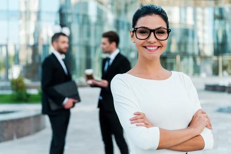 mujer trabajadora: confianza empresaria. joven empresaria manteniendo los brazos cruzados sonriendo y mirando a la c�mara mientras dos de sus colegas hombres hablando entre s� en el fondo Foto de archivo