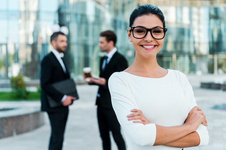 executive woman: Confident businesswoman. Smiling young businesswoman keeping arms crossed and looking at camera while two her male colleagues talking to each other in the background