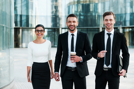 Great business minds. Three cheerful young business people looking at camera and smiling while standing outdoors Stock Photo