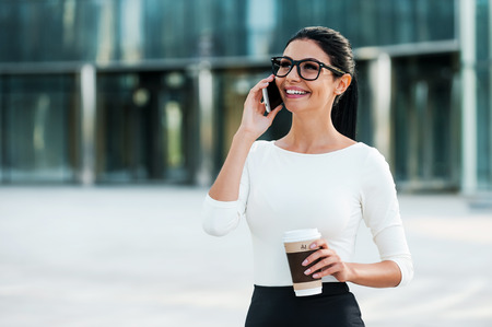 white collar worker: Good business talk. Cheerful young businesswoman talking on the mobile phone and holding cup of coffee while standing outdoors Stock Photo