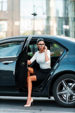 mujer desnuda sentada: Mujer mandona. Confianza empresaria joven hablando por teléfono móvil, al salir de su coche Foto de archivo