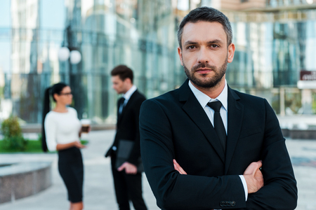office building: He is great team leader. Confident young businessman keeping arms crossed and looking at camera while two his colleagues talking to each other in the background