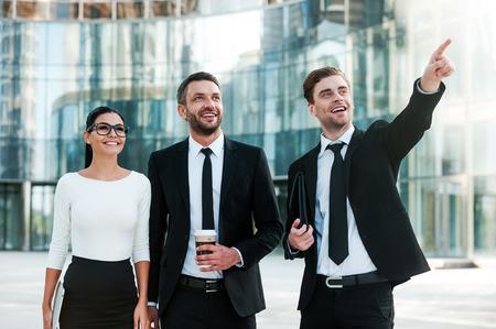 personas mirando: Trayendo nuevas ideas de negocio en la vida. Tres j�venes empresarios alegres mirando a otro lado y sonriendo mientras est� de pie al aire libre