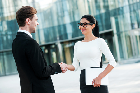 people shaking hands: Welcome on board! Two smiling young business people shaking hands while standing outdoors Stock Photo