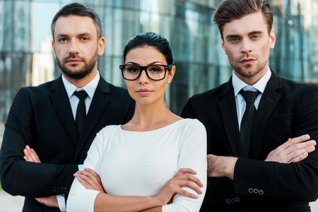 business manager: Faces of new business. Three confident business people keeping arms crossed and looking at camera while standing outdoors