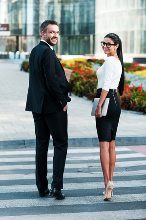 workday: Ready for this workday. Full length of two smiling business people looking at camera while crossing the street Stock Photo