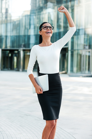 office worker: What a lucky day! Cheerful young businesswoman keeping arms raised and expressing positivity while standing outdoors Stock Photo