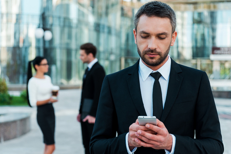 text message: Business texting. Serious young businessman holding mobile phone and looking at it while two his colleagues talking to each other in the background Stock Photo
