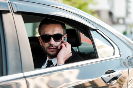 people   lifestyle: Confident and successful. Serious young businessman talking on the mobile phone while riding inside his car Stock Photo