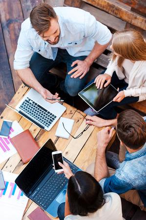 personas trabajando: Disfrutando de su trabajo creativo. Vista superior de cuatro jóvenes trabajando juntos mientras está sentado al aire libre