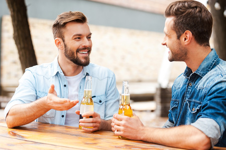 two men: Good talk with friend. Two joyful young men talking to each other and holding bottles with beer while standing outdoors