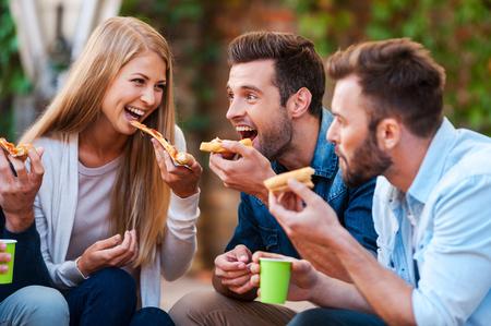 people: 피자 애호가. 함께 즐기면서 피자를 먹고 장난 젊은 사람들의 그룹 스톡 콘텐츠