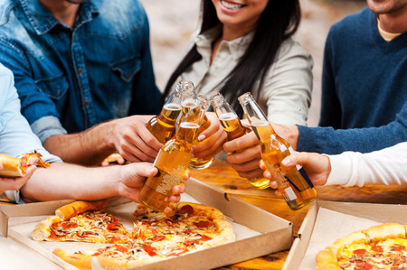 drinks on bar: Celebrating their friendship. Close-up of group of young people eating pizza and clinking glasses with beer while standing outdoors Stock Photo
