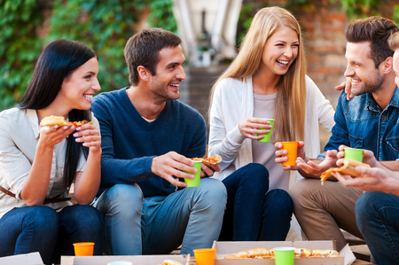personas: Pasar un buen rato con los amigos. Grupo de jóvenes alegres que hablan el uno al otro y comiendo pizza mientras sentado al aire libre