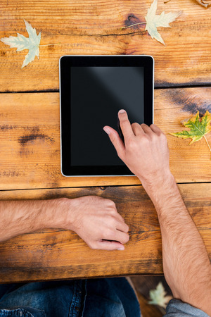 male hand: All the world in one touch. Close-up of man holding his finger on digital tablet while sitting at the wooden table outdoors