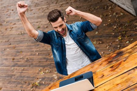 hombres jovenes: Ganador cotidiana. Vista superior del hombre joven emocionado manteniendo los brazos en alto y expresando positividad mientras est� sentado en la mesa de madera al aire libre