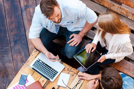 그들은 어디서든 작업 할 수 있습니다! 야외 앉아있는 동안 함께 작업 세 젊은 사람들의 상위 뷰