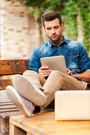 digital tablet: Confident and relaxed. Handsome young man working on digital tablet while sitting at the wooden table outdoors