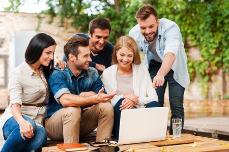 Es ist geniale Idee! Gruppe der frohen jungen Menschen auf der Suche Laptop, während im Freien zusammen arbeiten Standard-Bild - 45174914