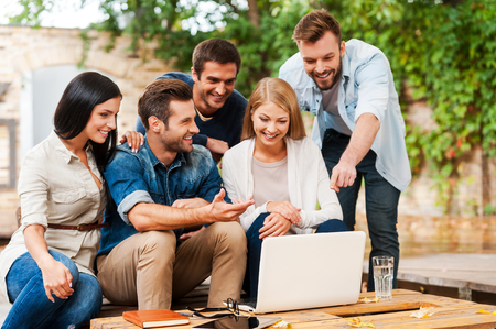 It is brilliant idea! Group of joyful young people looking at laptop while working together outdoors Stock Photo