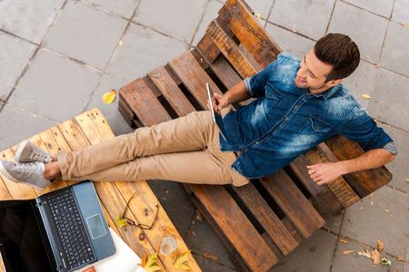 서두르고없이 사업. 야외 휴식하는 동안 디지털 태블릿을 들고 젊은 웃는 남자의 상위 뷰