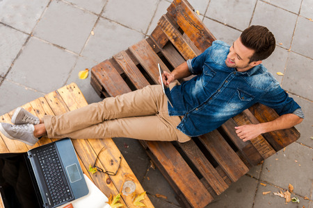 relaxing: Business without hurrying. Top view of smiling young man holding digital tablet while relaxing outdoors Stock Photo