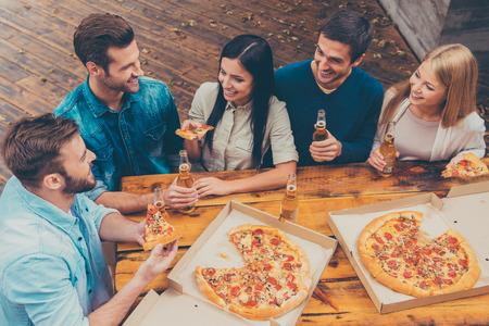 함께 시간을 즐기고있다. 다섯 행복 젊은 사람들 야외 서있는 동안 맥주 병을 들고와 피자를 먹는 상위 뷰