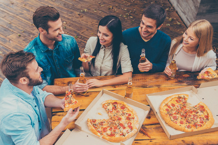 bar top: Enjoying time together. Top view of five happy young people holding bottles with beer and eating pizza while standing outdoors Stock Photo