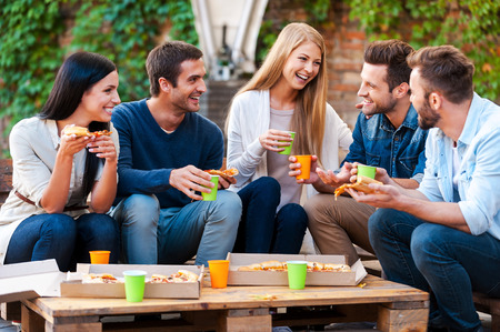 Quality time met vrienden. Groep van vrolijke jonge mensen met elkaar praten en het eten van pizza terwijl buiten zitten