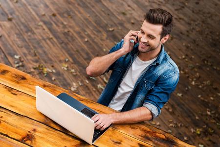 uomo felice: Affari su aria fresca. Vista felice giovane che lavora sul computer portatile e di parlare al cellulare phonewhile seduto al tavolo di legno all'aperto