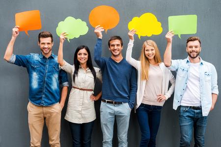 グローバル ・ コミュニケーション。空の吹き出しを押しながら灰色の背景に対して立ったままカメラ目線の幸せな若者のグループ